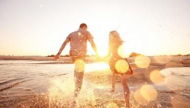 happy couple running on the beach; Shutterstock ID 133463087